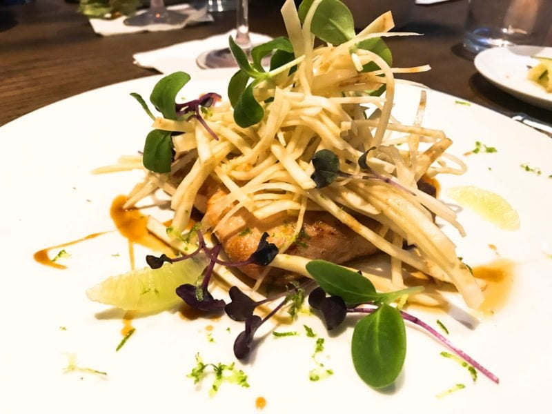 A chicken dish with microgreens on top.