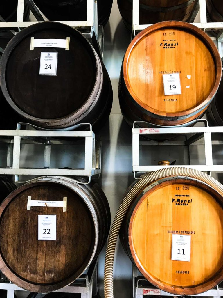 Two types of wood barrels on a shelf for aging balsamic vinegar.