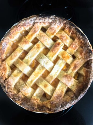 This peach Bellini pie recipe is made with market fresh summer peaches poached in sweet Moscato wine and baked in a buttery, flaky, lattice-top crust.