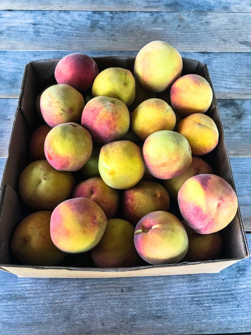 Box of peaches on a wooden table