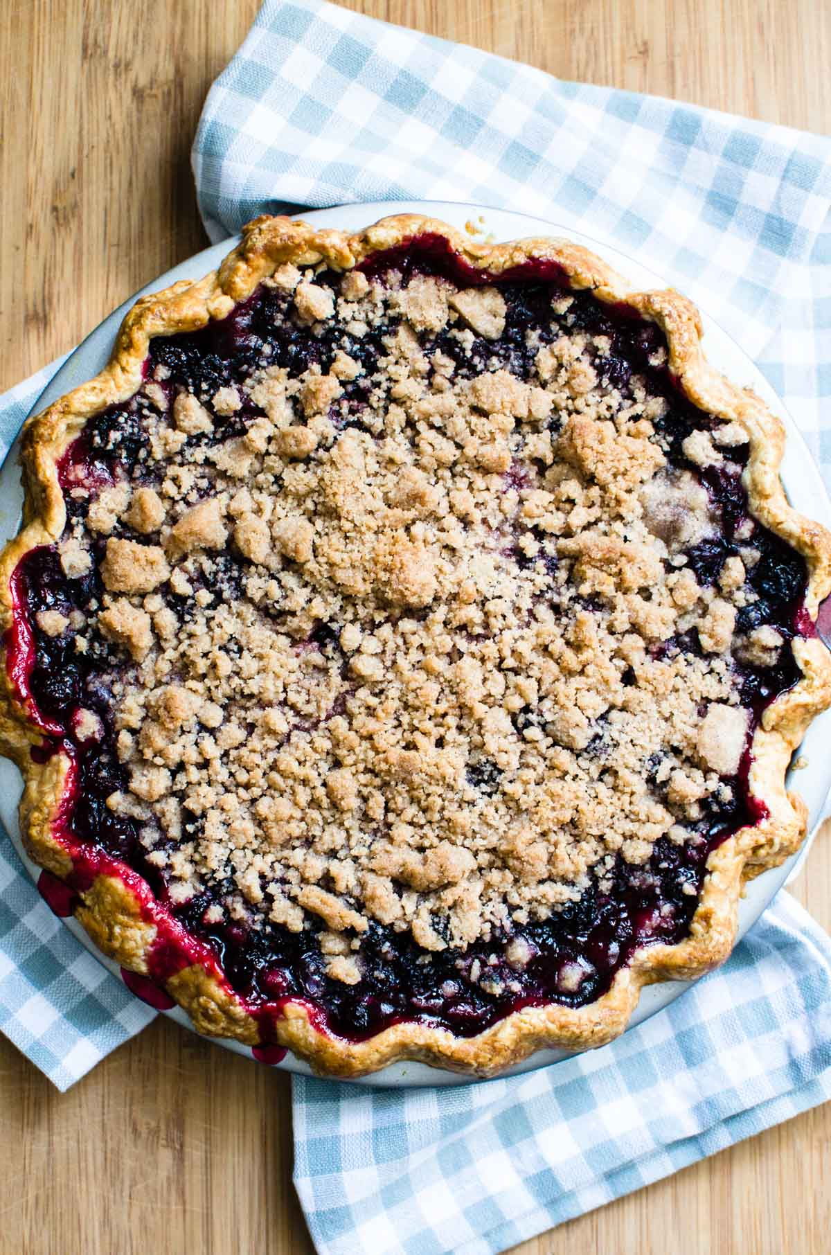 Mixed berry crumble pie just out of the oven on a wood board.