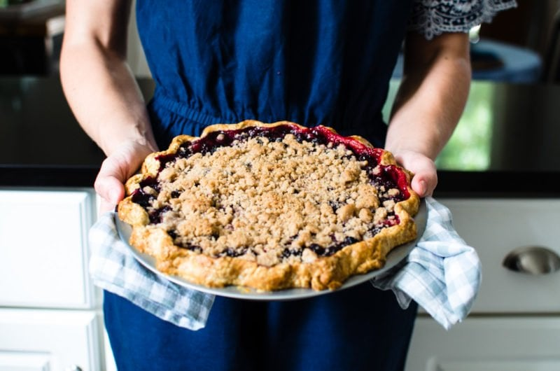 Chef holding mixed berry pie.