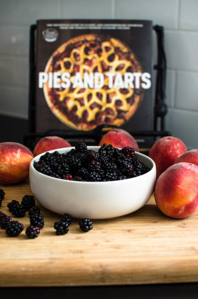 Bowl of blackberries surrounded by peaches with cookbook in background.