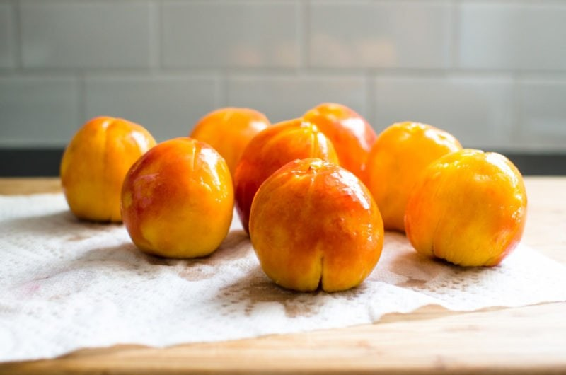 Cutting board with poached and peeled peaches.