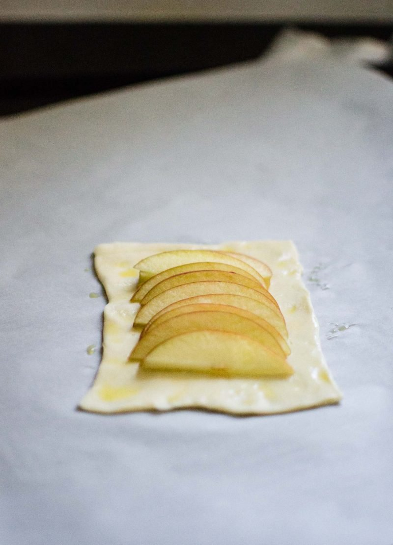 Pastry square with sliced apple on top. A step in making apple tart.