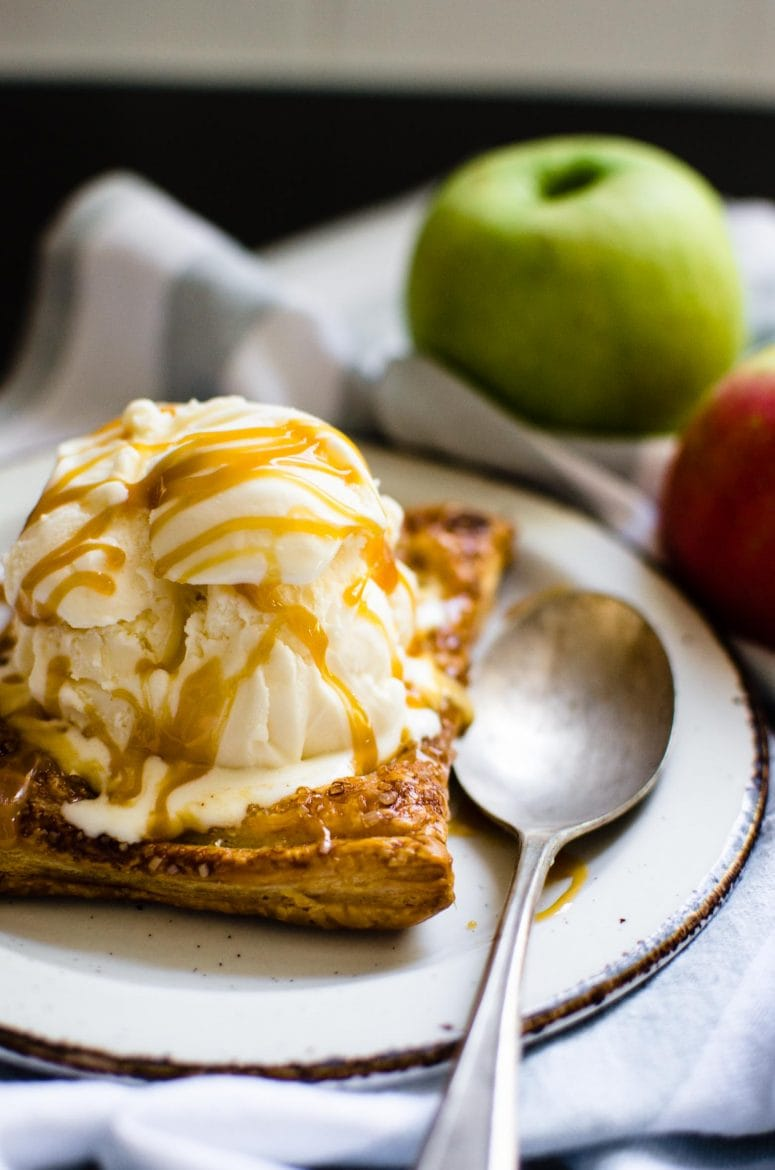 Photo of an apple tart topped with vanilla ice cream and caramel syrup.