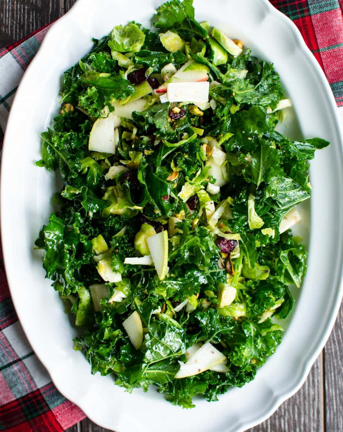 A festive kale salad with Brussels sprouts, apples, cranberries, pistachios, Parmesan, and a sweet + tangy apple cider vinaigrette. Tips on how to style a salad for a holiday party.