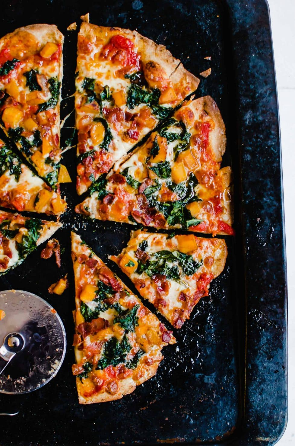This recipe for Kale, Bacon, and Butternut Pizza with Hot Honey Drizzle is a perfect way to enjoy pizza with fresh winter produce. It's baked on a whole wheat pizza crust and topped with a sweet and spicy drizzle!