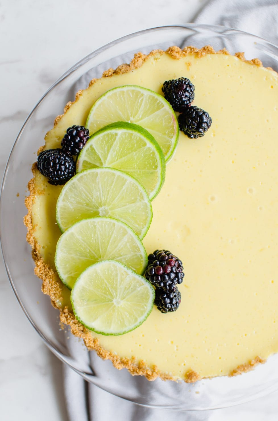 This recipe for a fresh lime tart has a buttery graham cracker crust and beautiful fresh blackberry sauce on top. It is very easy to make and would be perfect for St. Patrick's Day or Easter! #baking #sweetcayenne