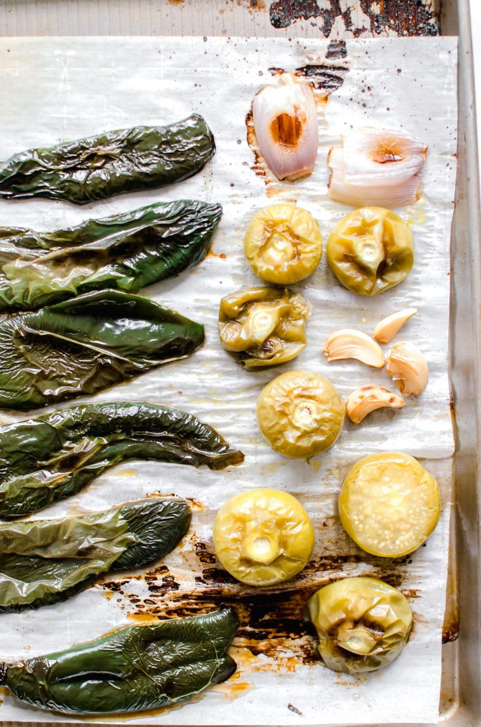 A cooking tray with roasted poblanos, garlic and tomatillos.