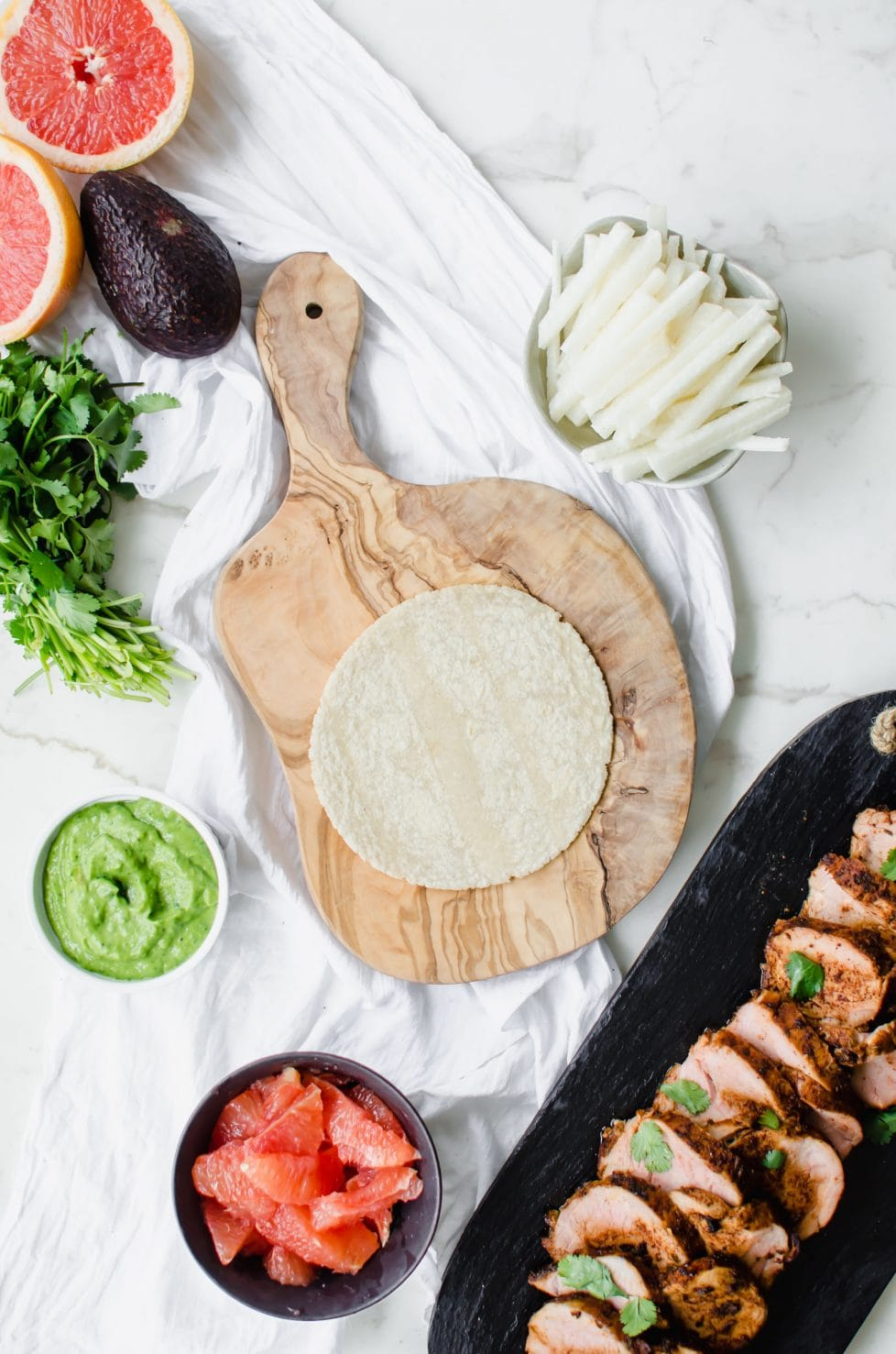Olive wood cutting board with a corn tortilla and other tacos fillings.