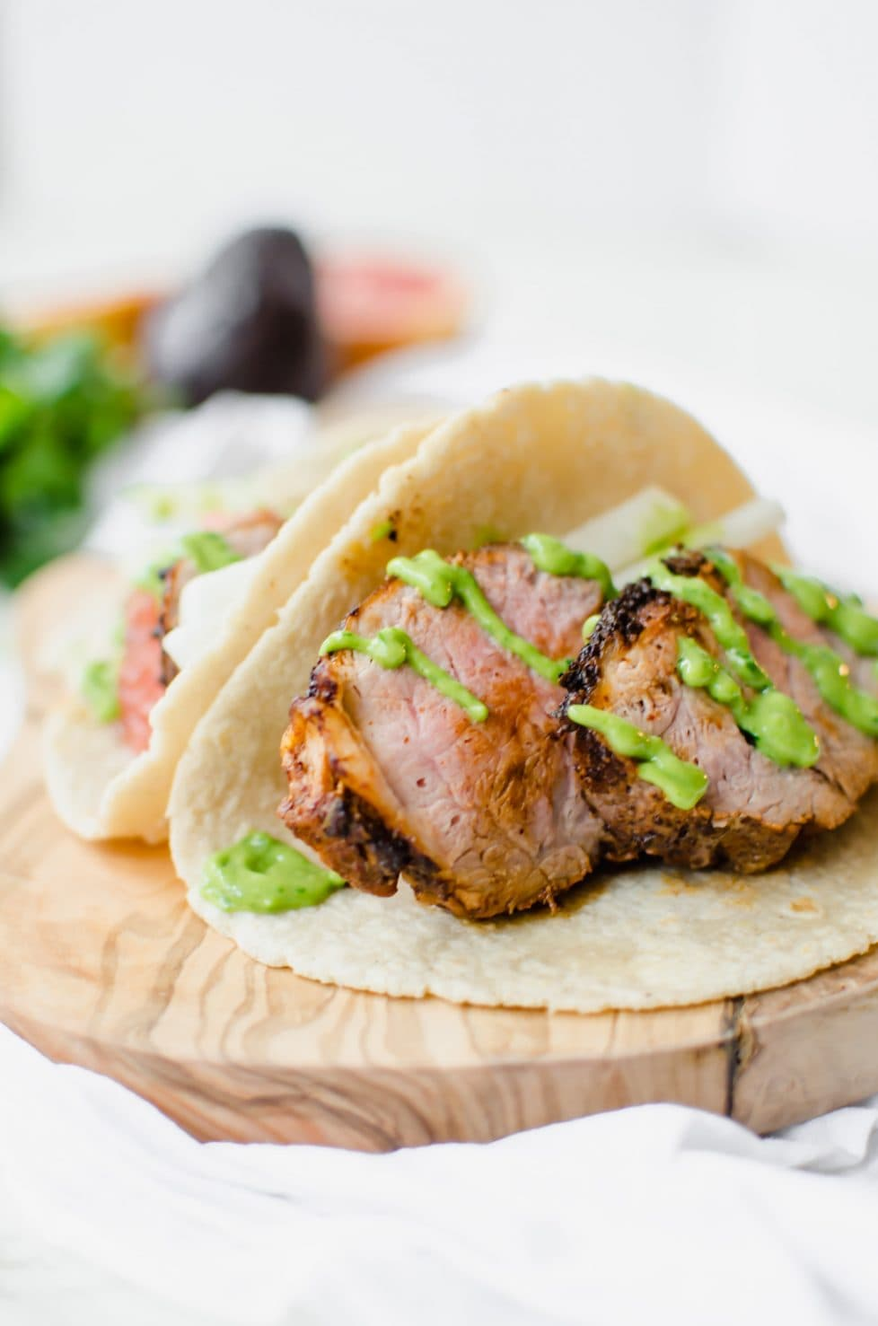 This recipe for Pork Tenderloin Tacos with Creamy Avocado Sauce is perfect for #tacotuesday and is an easy, healthy pork recipe you can roast in the oven.