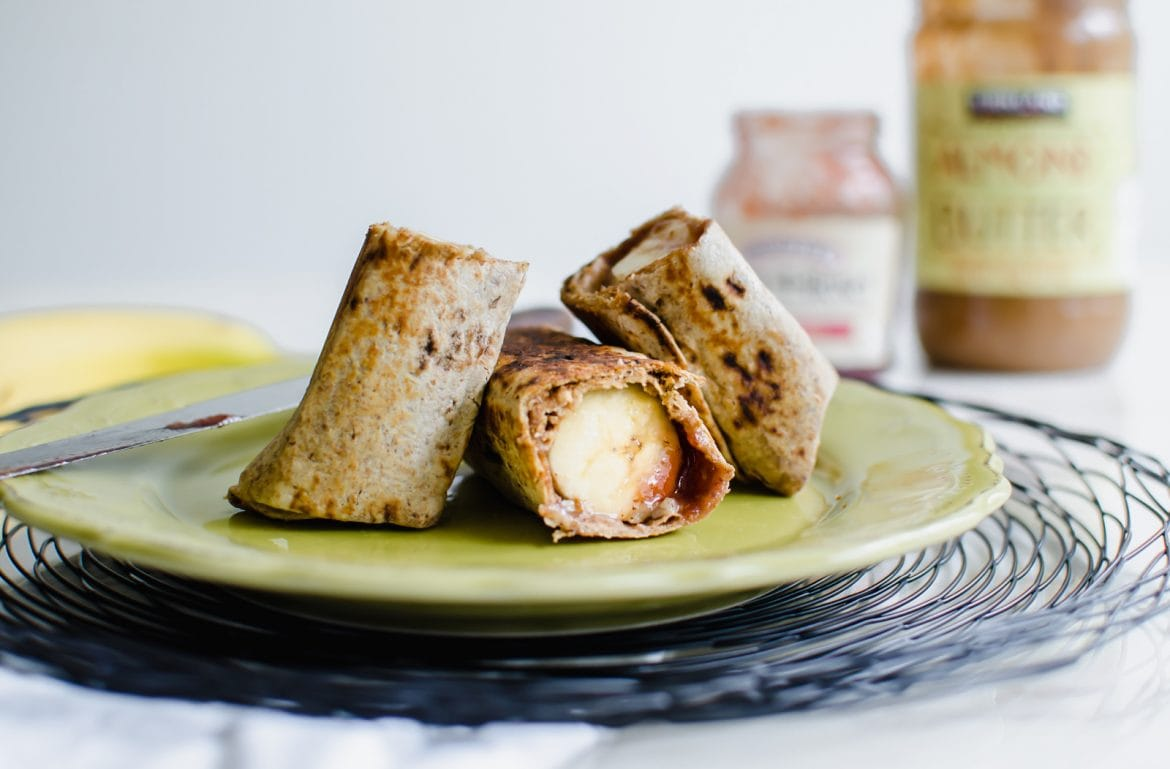 Straight-on shot of a whole grain wrap with a banana, almond butter, and jam inside sitting on a green plate.