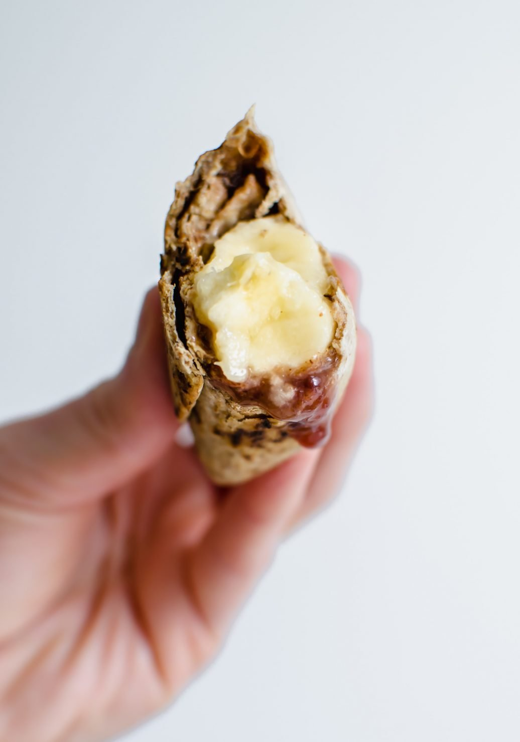 Straight on view of a hand holding half of a whole grain almond butter wrap with a banana inside against a white background.