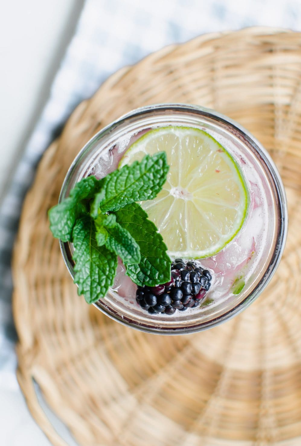 Overhead shot of a mason jar filled with a blackberry drink, lime slice, mint sprig, and blackberry. The jar is sitting in a woven basket tray on top of a green gingham tea towel.