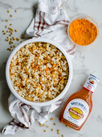 Overhead shot of a white bowl filled with buffalo cheddar popcorn on top of a white marble background with a container of cheddar cheese powder and a bottle of buffalo sauce.