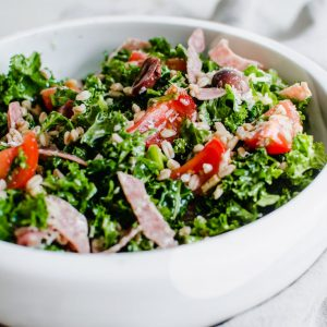 Overhead side photo of Italian Kale salad topped with veggies and sliced meat.
