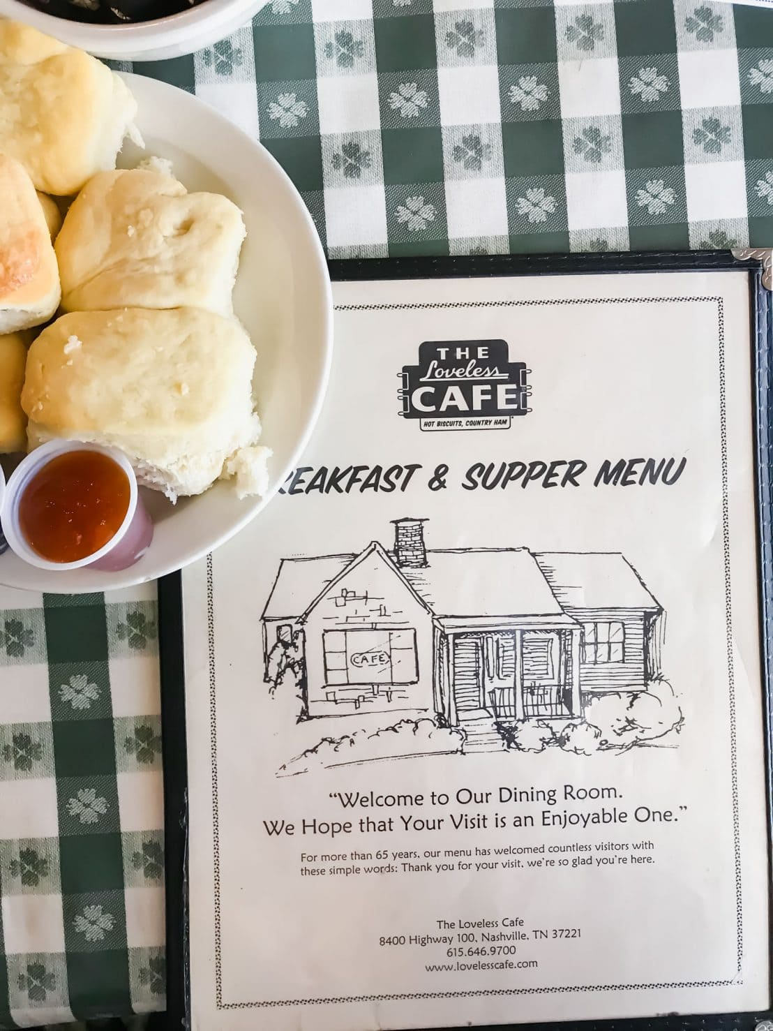 A menu for the Loveless Cafe sitting on a checkerboard tablecloth with a plate of biscuits to the side.