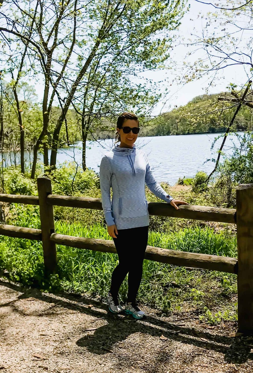 A young woman standing in front of a wooden fence with a lake background on a sunny day.