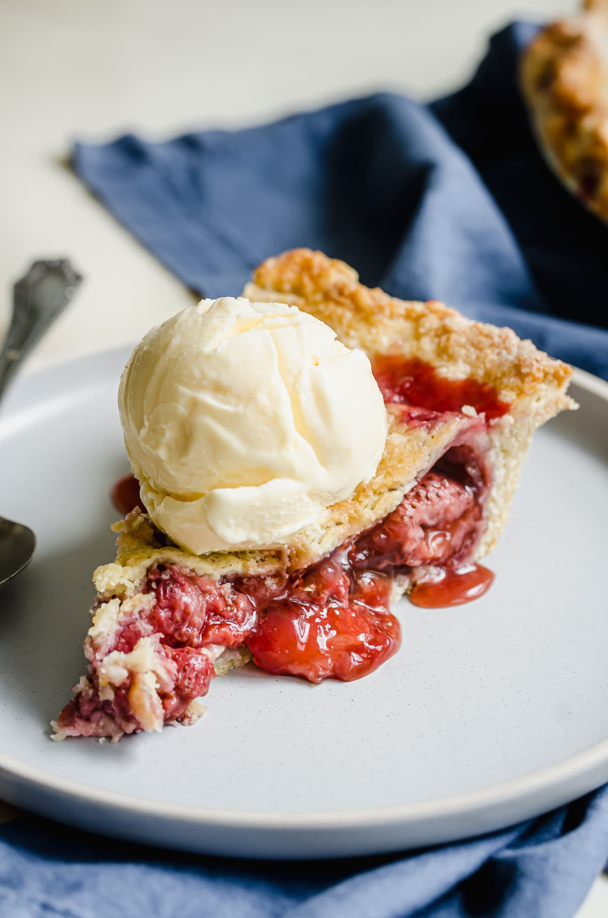 A double crust slice of strawberry pie topped with ice cream.