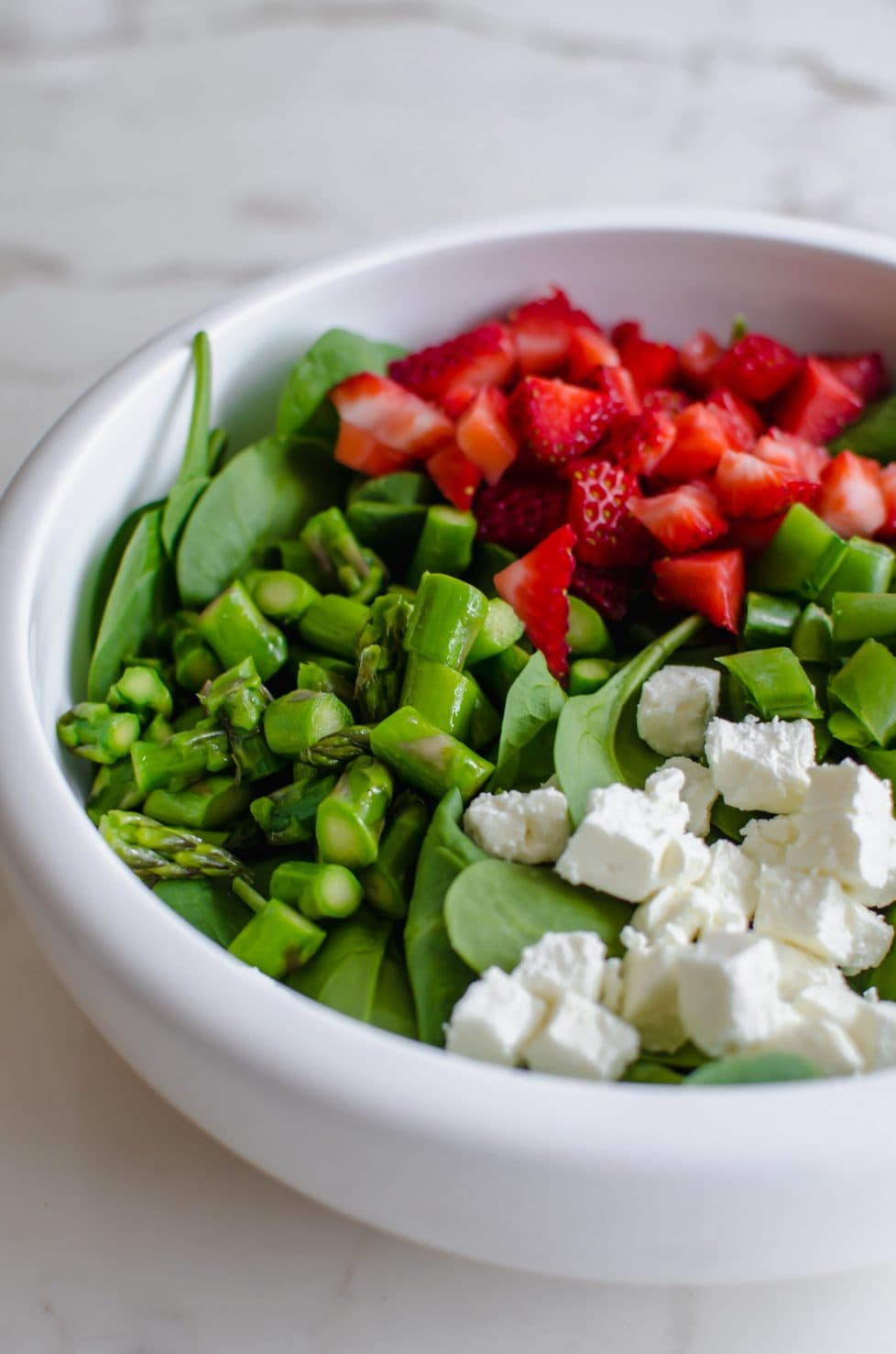 A white bowl with salad.