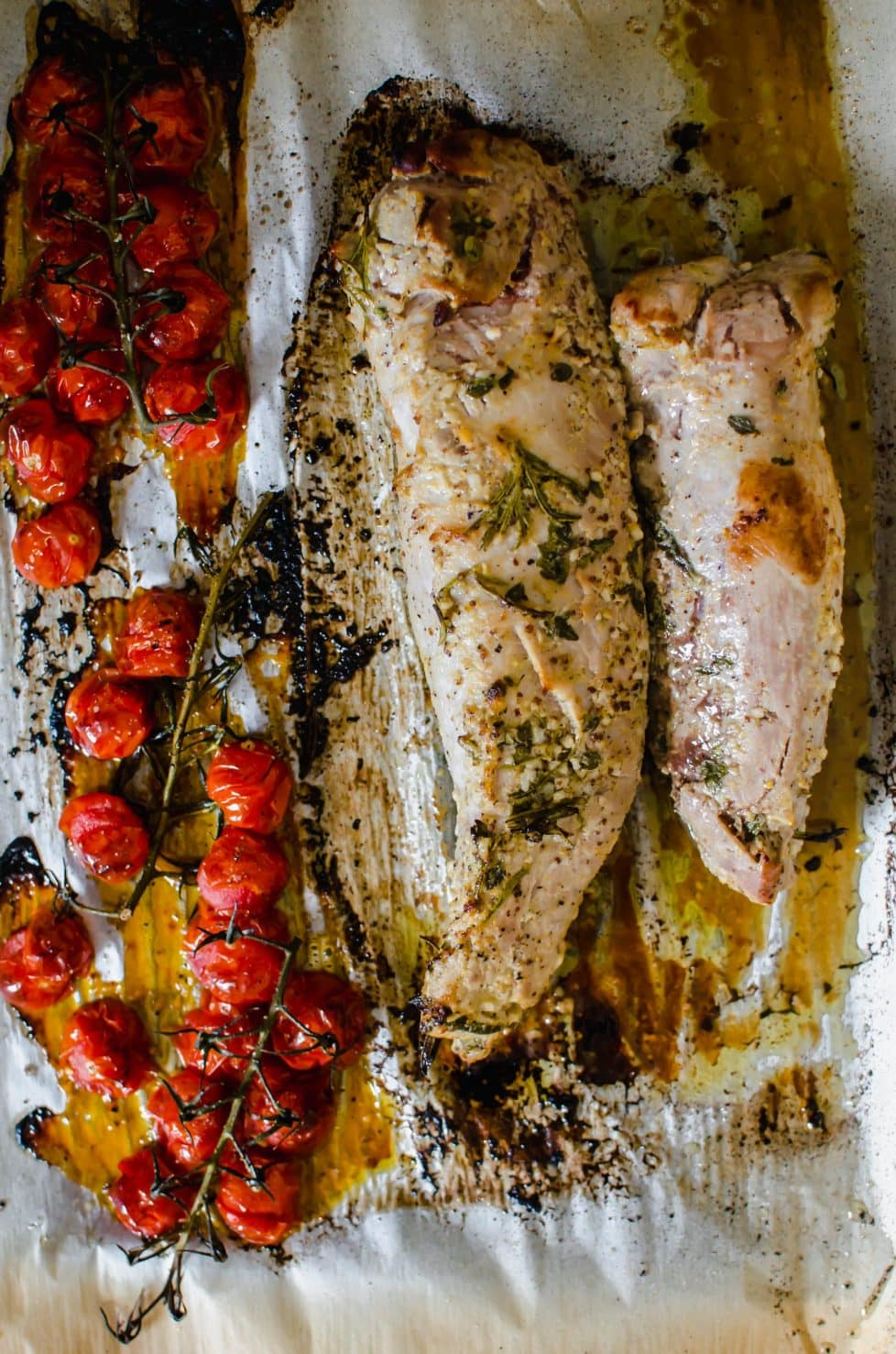 A sheet pan with pork and blistered tomatoes.