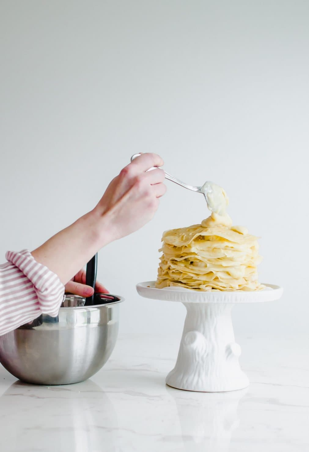 Side view of a woman's hand placing a spoonful of pudding on top of a crepe cake on a white cake pedestal.