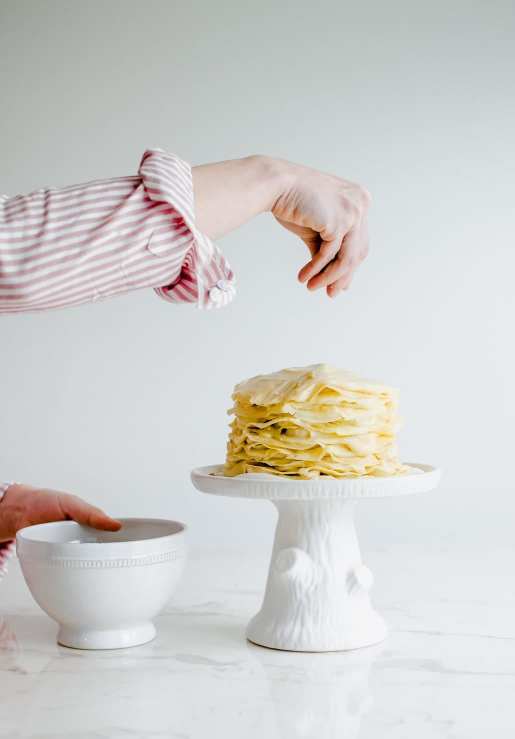 Side view of a woman's hand placing cookie crumbs on a banana pudding crepe cake agains a white background.