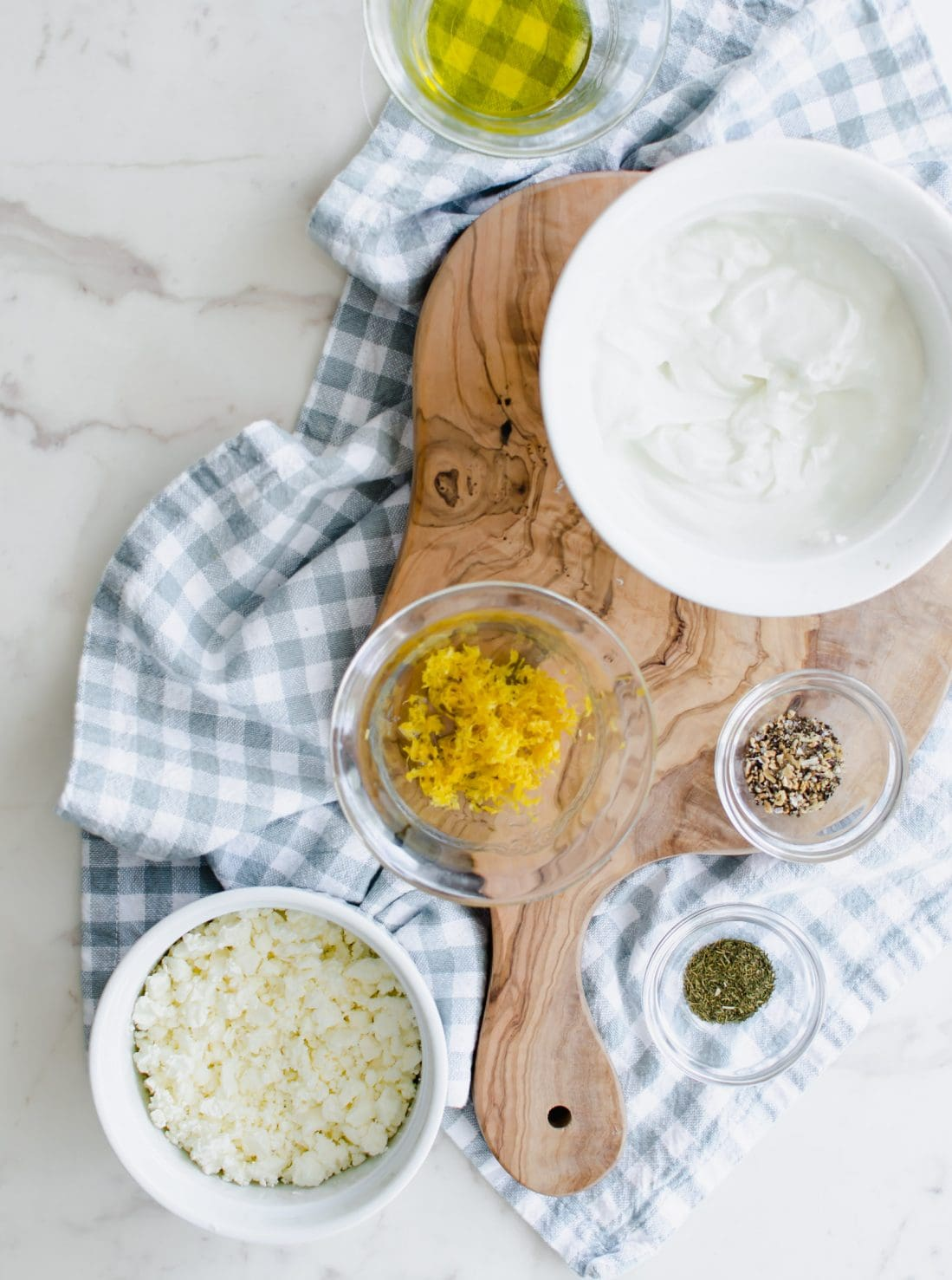 An overhead shot of bowls with ingredients for making a feta dipping sauce on a white marble counter top.