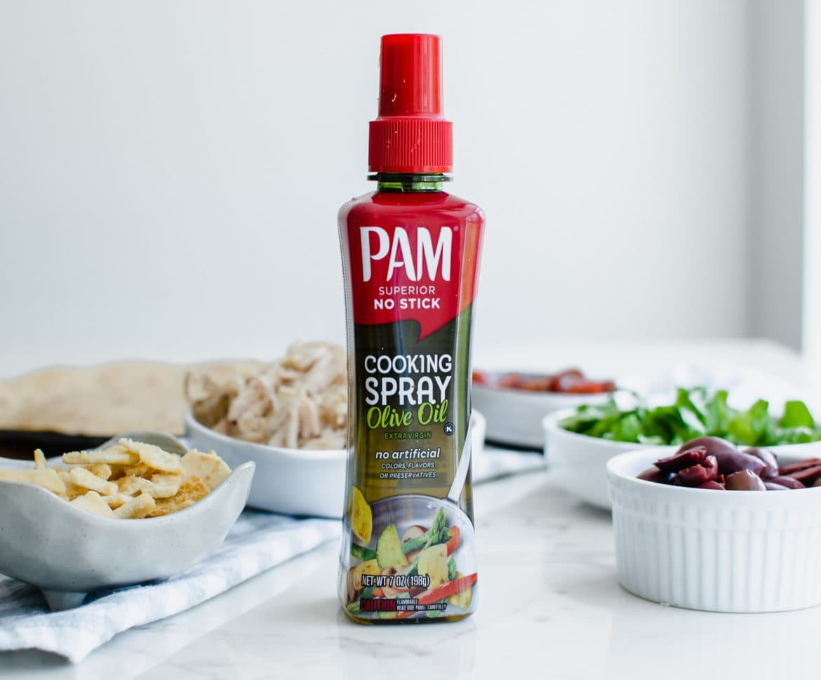 A bottle of PAM non-aerosol olive oil spray with white bowls of Greek salad toppings on a white marble counter.
