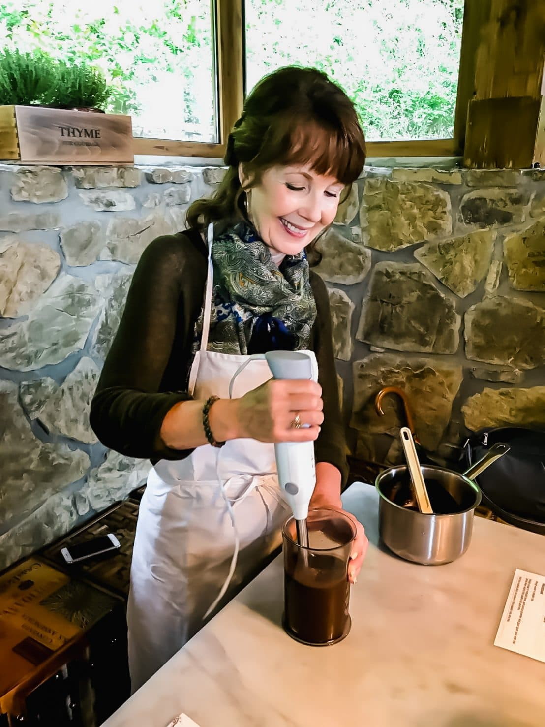 A woman making gelato and mixing with an immersion blender.