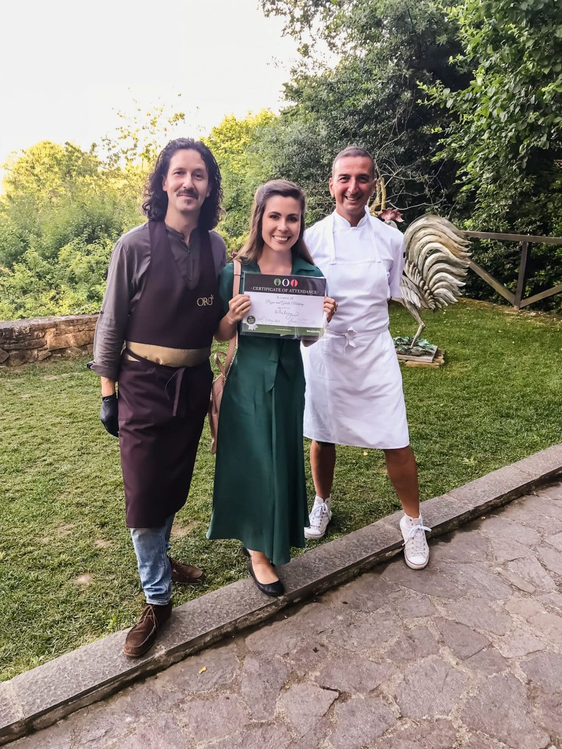 A girl in a green dress holding a cooking class certificate with two Italian chefs.