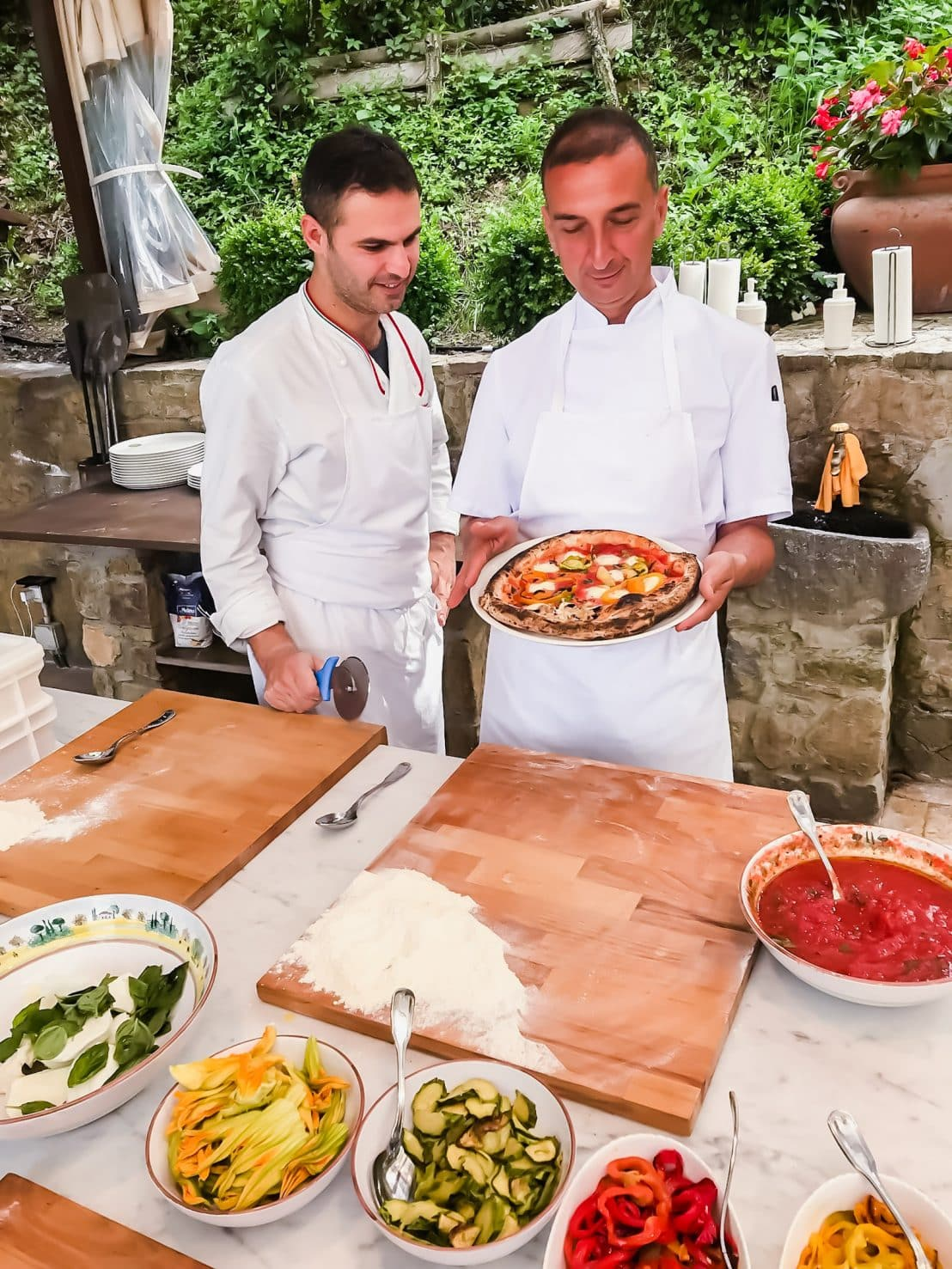 A photo of two Italian chefs doing a pizza cooking demonstration outdoors.