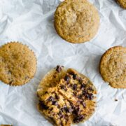 An overhead shot of Moka Chocolate Chip Muffins on wrinkled white parchment paper with one muffin broken in half.