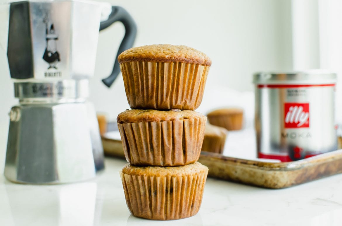 A straight-on shot of a stack of chocolate chip muffins with a stovetop mocha pot and Illy coffee can in the background.