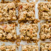 An overhead shot of Pecan Butter and Peach Jam Crumble Bars sitting on white parchment paper.