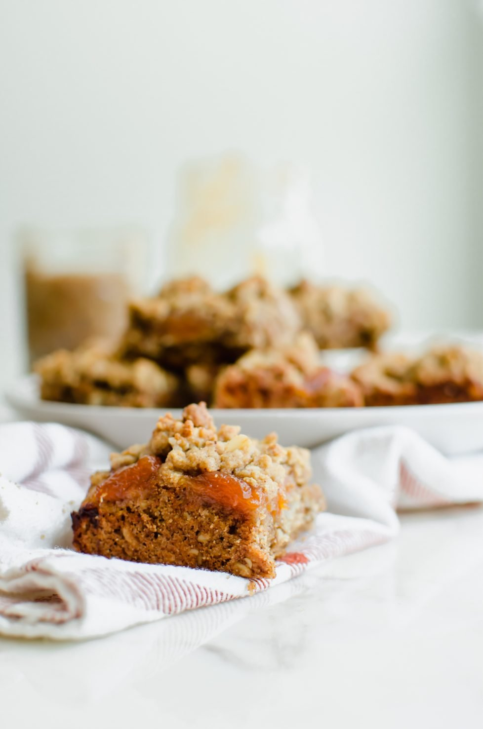 A side shot of a Pecan Butter and Peach Jam Crumble Bar sitting on a plaid kitchen towel with a white plate of bars in the background.