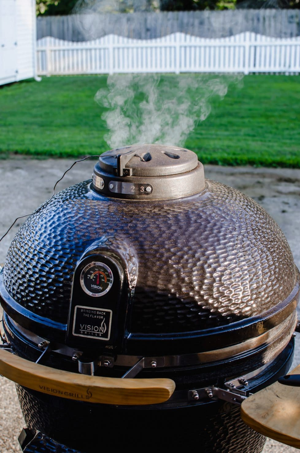 A shot of the top of a kamado grill with smoke coming out of the top vent.