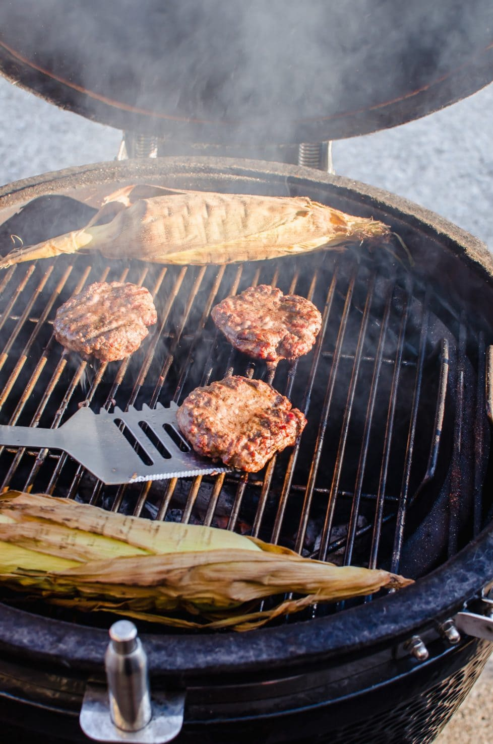 Burger patties being flipped on a grill with two ears of corn in the shuck.