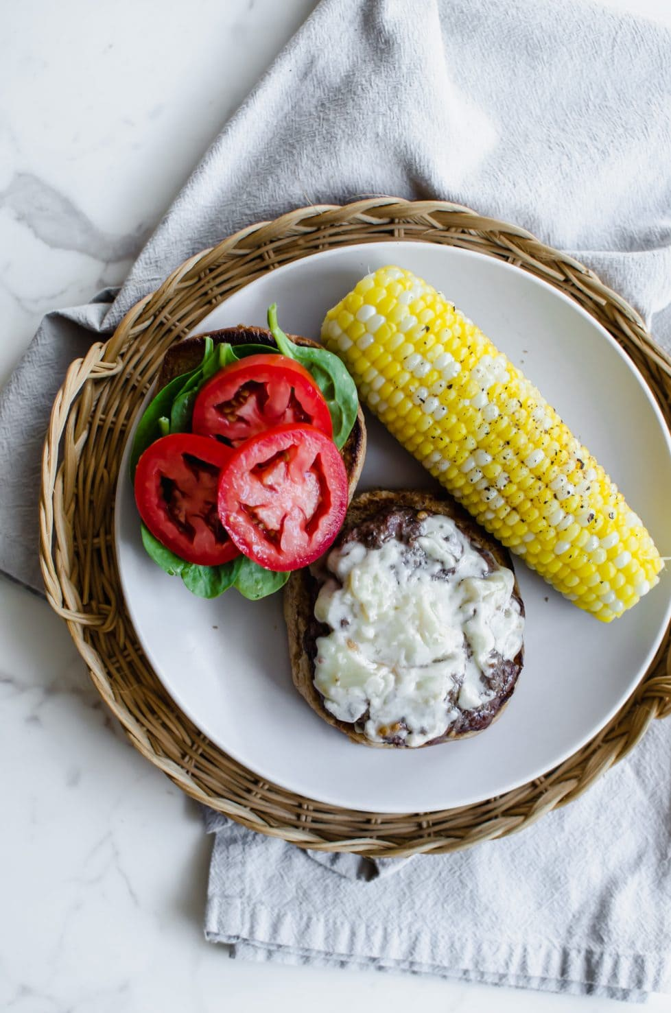 A view from above of an open-faced burger with sliced tomato, spinach, white cheddar, and an ear of corn on the side.