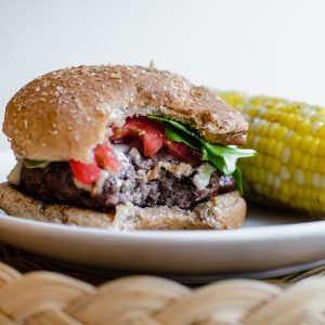 A burger topped with spinach and tomato with a bite taken out of it and an ear of corn on the side.