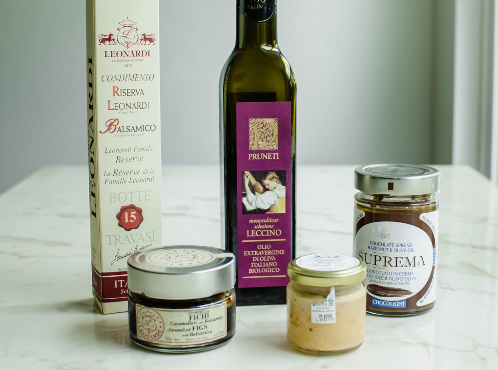 A row of Italian food products - including olive oil, balsamic vinegar, fig spread, Parmesan truffle spread, and chocolate sauce on a white marble countertop.