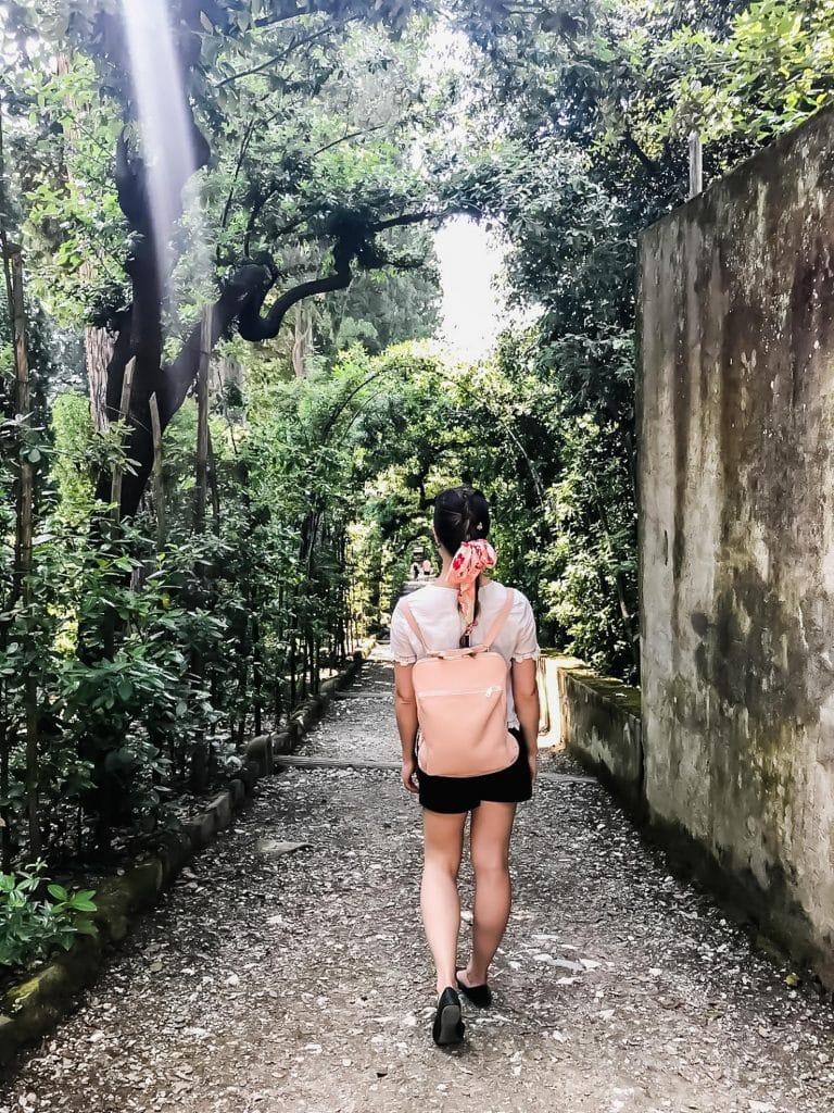 A girl walking down a garden path in Italy.