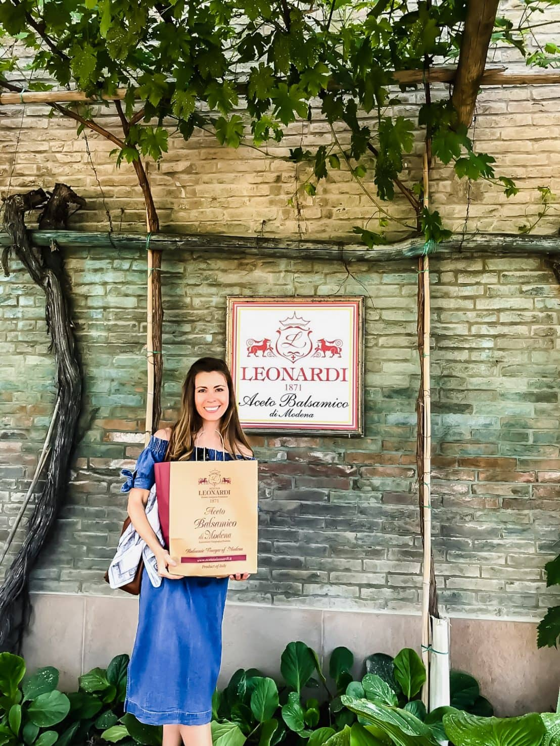 A young woman holding a shopping bag in front of a brick wall with a sign for Leonardi balsamic.