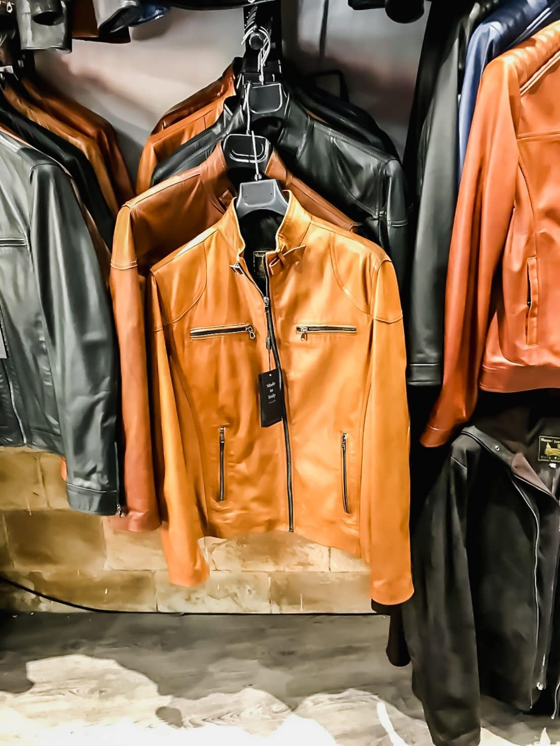 A photo of a row of leather jackets for men in a store.