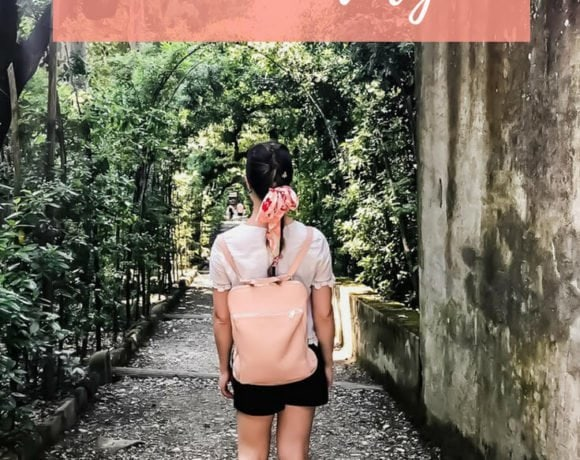 A girl wearing a pink backpack walking down a gravel path surrounded by trees.