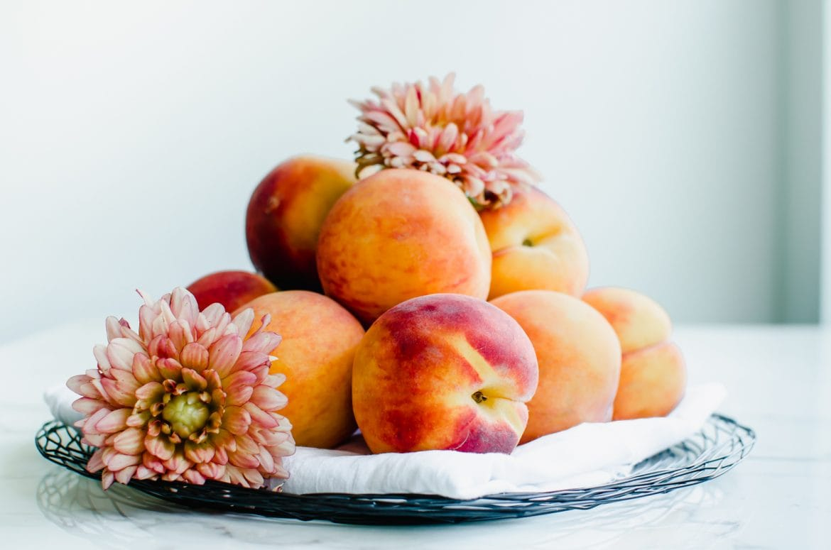Fresh peaches piled on a wire plate with a white towel and coral dahlias sitting on the peaches.