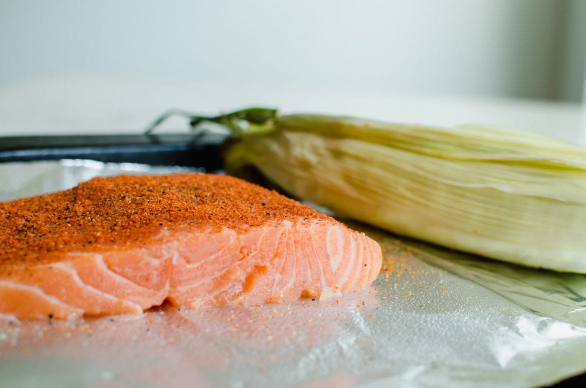 A piece of raw salmon on a sheet pan with a piece of corn in the shuck.