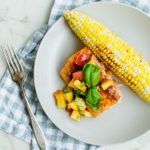 A piece of BBQ salmon on a beige plate topped with peach salsa and an ear of roasted corn on the side.