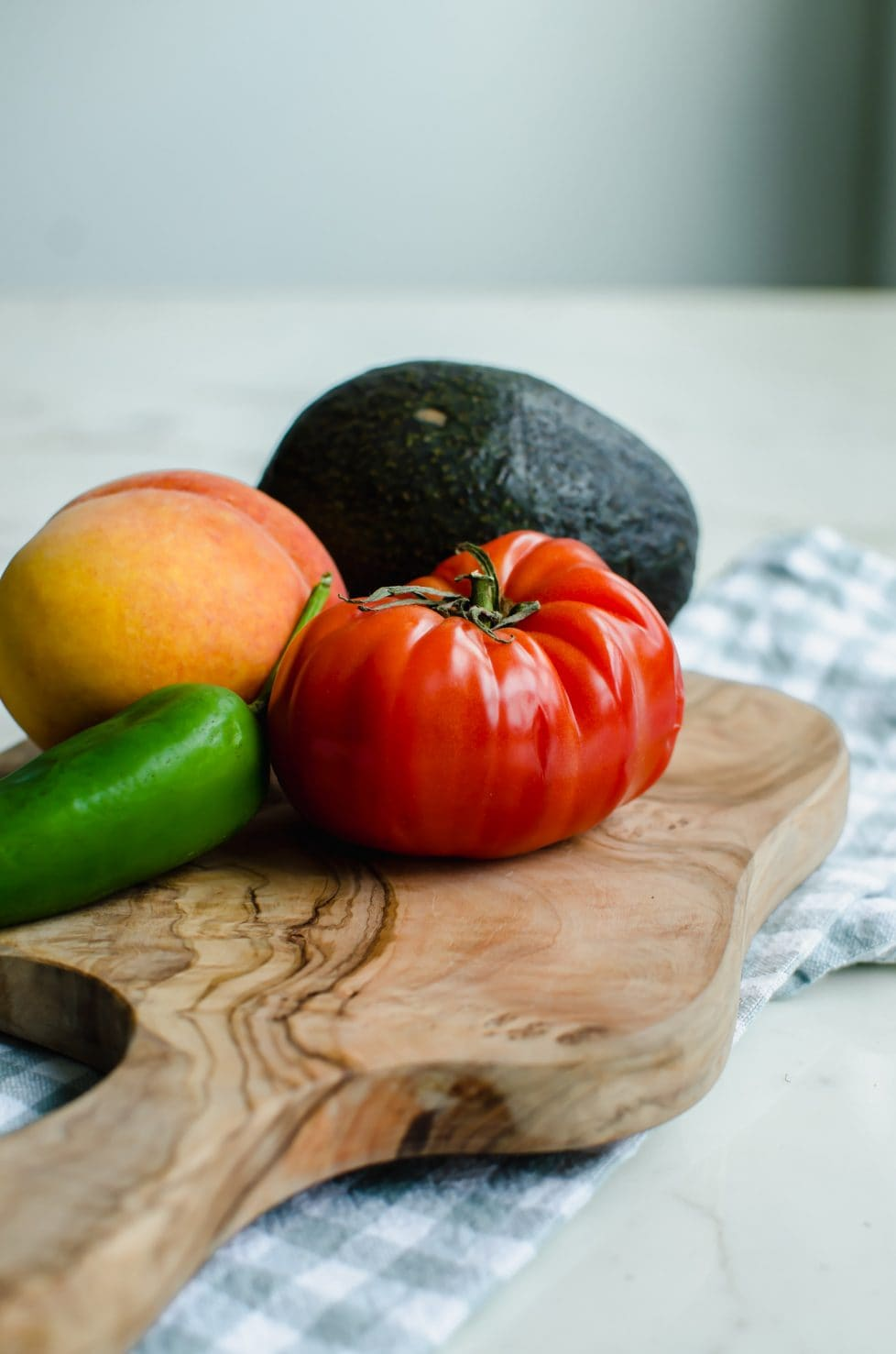 A cutting board with a fresh tomato, avocado, peach, and jalapeño.
